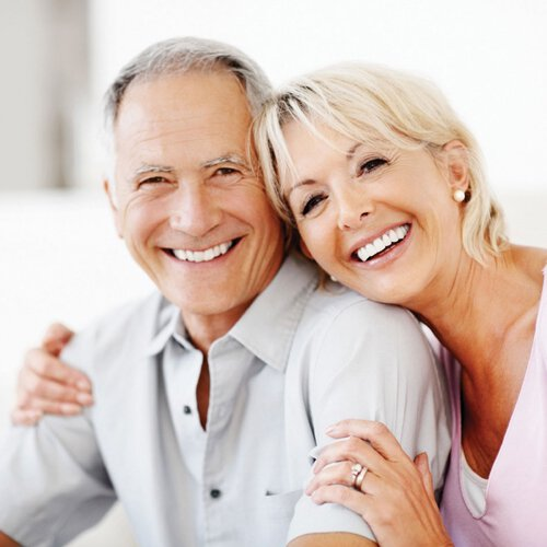 older couple smiling with their dentures in